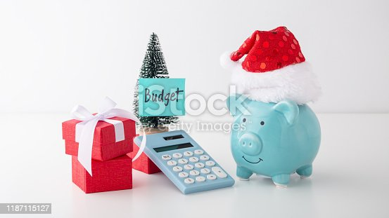 Christmas budget and saving concept, piggy bank with christmas hat, decoration and calculator on white table