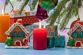 New Year background with Christmas decorations with fir and pine branches, gingerbread house, burning candle and colorful balls and garlands.
