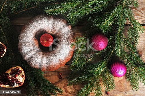 Fir branches on a wooden background. Among the branches is a Christmas cake decorated with a candle. Next to several New Year's toys and half a pomegranate. Top view. Close-up.
