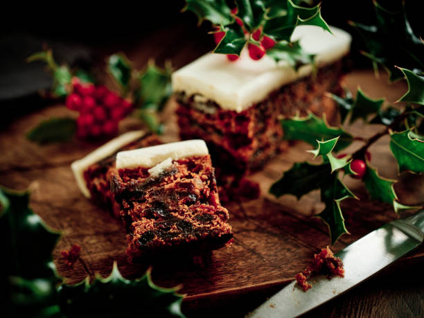 Christmas Cake on a dark rustic wood surface surrounded by freshly picked Holly.
