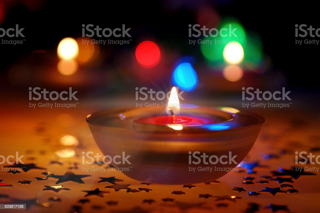 christmas candle and colorful lights stock photo