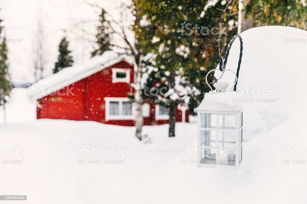 Kerst kaars in lantaarn. Rode houten vakantiehuis in landelijke besneeuwde Finland. - Royalty-free Achtergrond - Thema Stockfoto