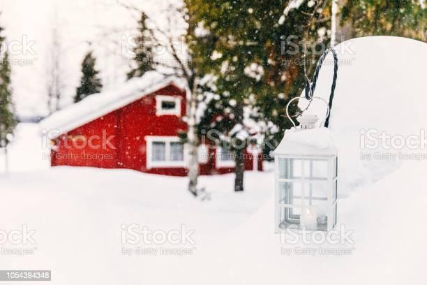 Kerst Kaars In Lantaarn Rode Houten Vakantiehuis In Landelijke Besneeuwde Finland Stockfoto en meer beelden van Achtergrond - Thema