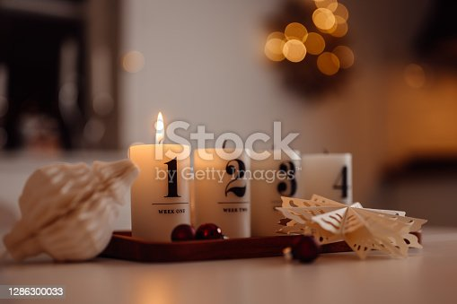 Christmas candle lights first advent on table indoors infront of christmas tree Photo taken indoors in candle light of burning first light scandinavian style