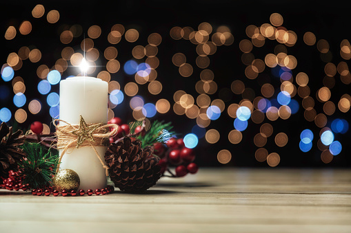Christmas candle lights on rustic wooden table and copy space. Christmas themes.