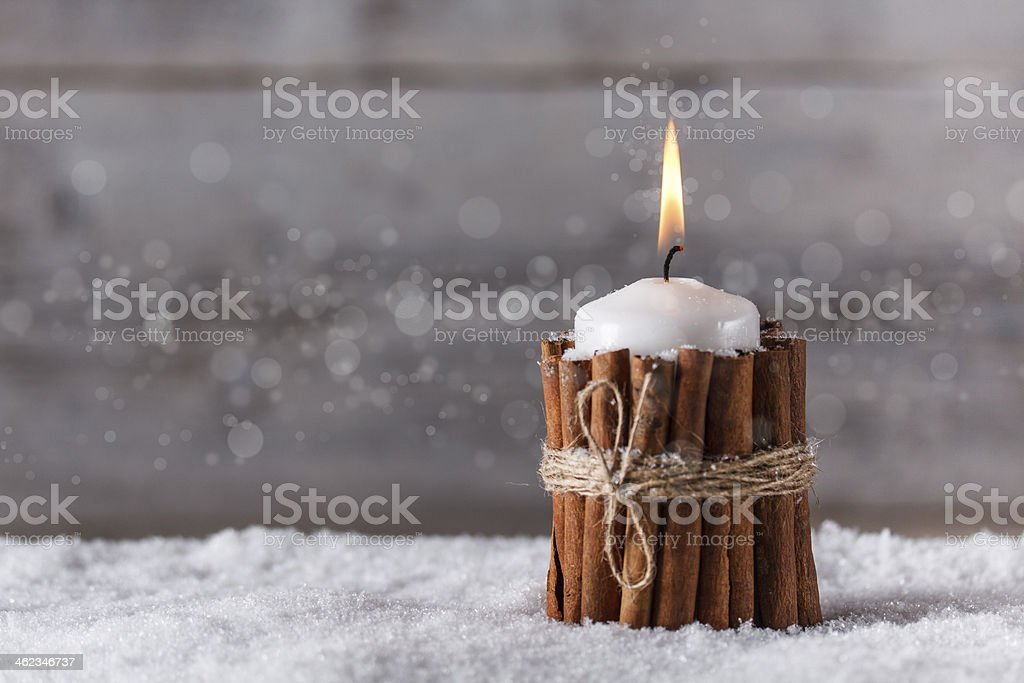 Christmas candle wrapped in cinnamon sticks in the snow - Royalty-free Candle Stock Photo