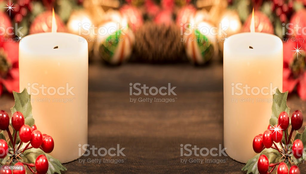 Christmas candles with holly and decorations. stock photo