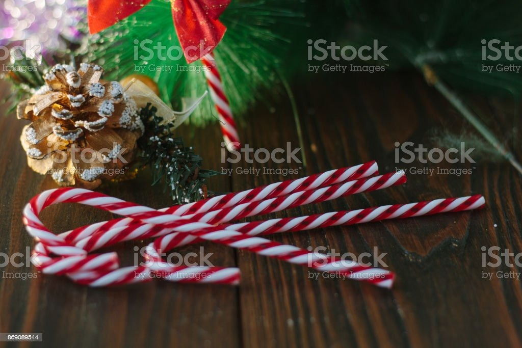 Christmas candy canes with the fir-cone as christmas background. stock photo