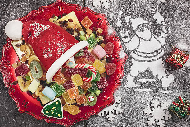 Christmas candy dessert Sweet Sugar Santa Hat cone, filled with Sweets and Santa made of snow spray over gray background. Done with a vintage retro filter jujube candy stock pictures, royalty-free photos & images