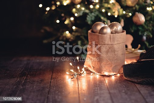 istock Christmas canvas bag with balls and lights on the dark boards, the New year concept 1072526096