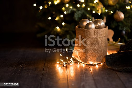istock Christmas canvas bag with balls and lights on the dark boards, the New year concept 1072526102