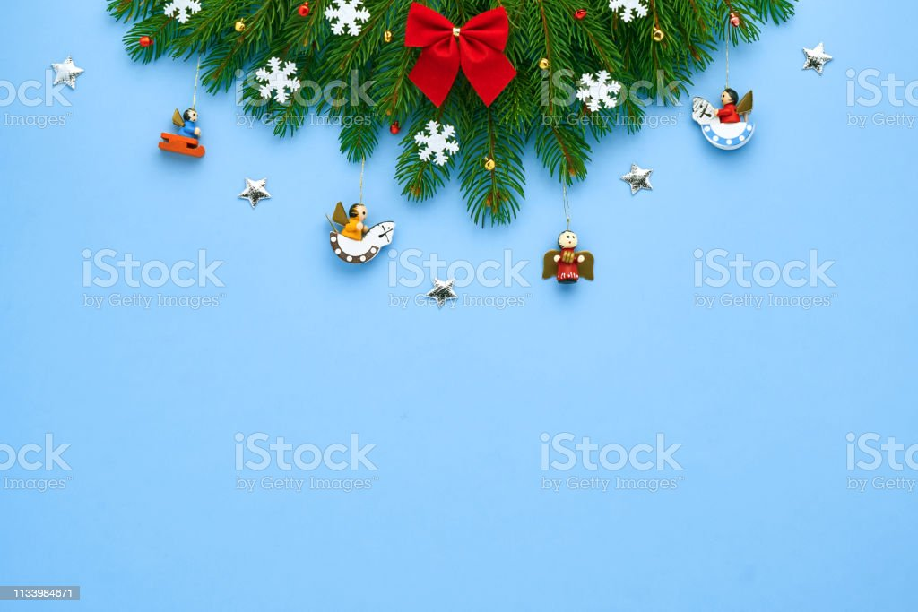 Christmas card. Branches of Xmas tree, folded in a triangle, decorated with a red bow, white snowflakes, bright stars, small bells, on a blue festive background. Background for your text and design stock photo