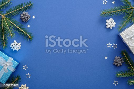 istock Christmas card concept with fir tree branches, presents, snowflakes, decorations on blue background. Christmas or New Year frame composition. Holiday and celebration mockup for postcard or invitation. 1165123908