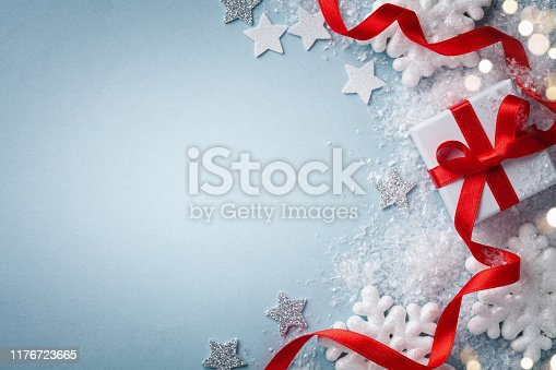 1076063742 istock photo Christmas card. Gift or present box with red ribbon and holiday decoration on blue background top view. Happy New Year composition. 1176723665