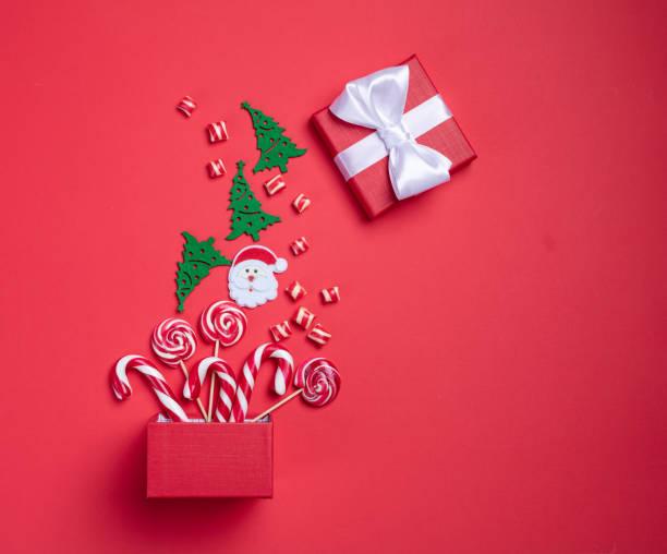 Weihnachtskarte. Einladungskarte auf rotem Hintergrund. Überraschungsbox mit Süßigkeiten. Interessantes Angebot für Sie. – Foto