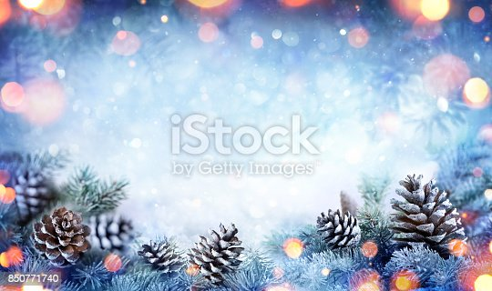 istock Christmas Card - Snowy Fir Branch With Pine Cones And Lights 850771740
