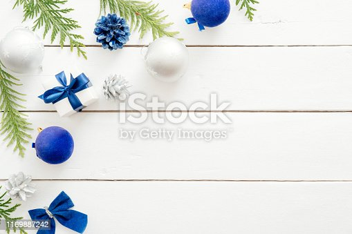 istock Christmas card with blue balls, fir tree branches, gift boxes, ornaments on wooden white background. New year holiday festive banner mockup. Christmas card template. Flat lay, top view, overhead 1169887242