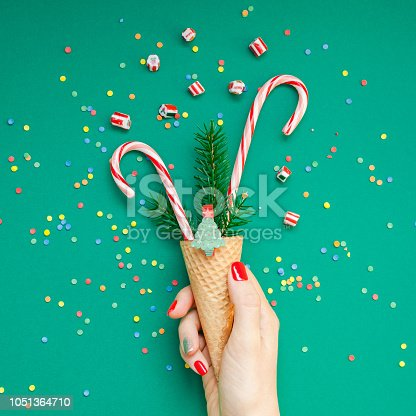 New Year Christmas Xmas holiday celebration woman hand red manicure holding waffle cone candy canes fir tree branch copy space green color paper background. Square Template greeting card 2019