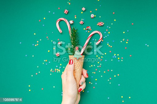 istock Christmas card with candy canes in waffle cone 1055997614