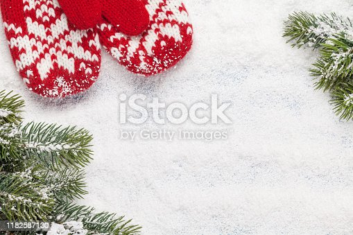 Christmas greeting card with fir tree and mittens over snow background. Top view with space for your greetings. Flat lay