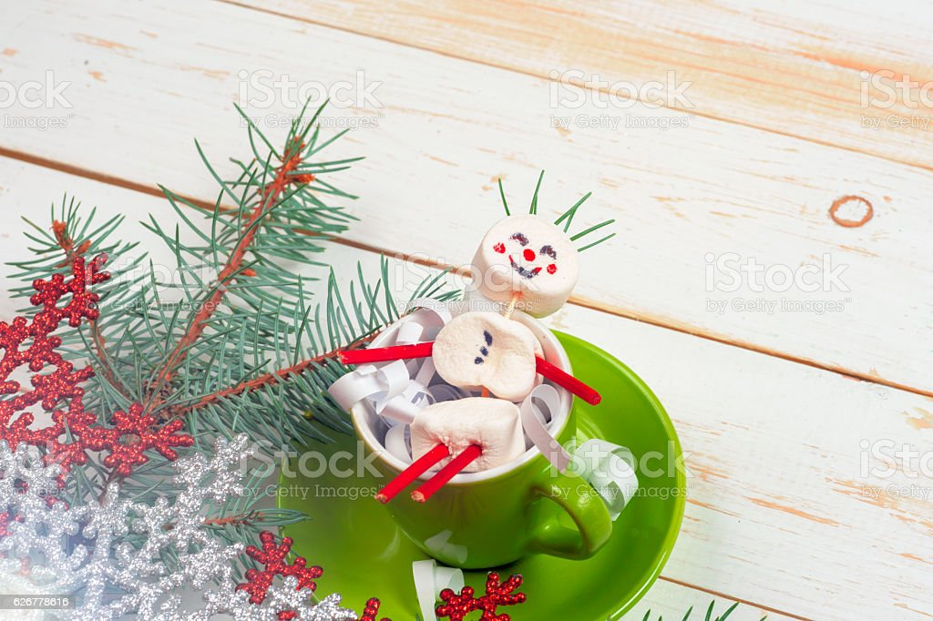 Christmas card with fun marshmallow snowman in green cup, Christmas...