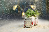 istock Christmas card with little vintage bus with christmas tree on the roof. Car sneaks through the snowfall. Christmas background. 1162161914