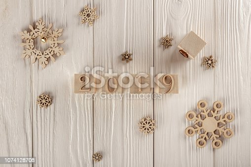 1009979852 istock photo Christmas card, wooden cubes on a wooden background. Home cozy design. Happy new year 2019. 1074128708