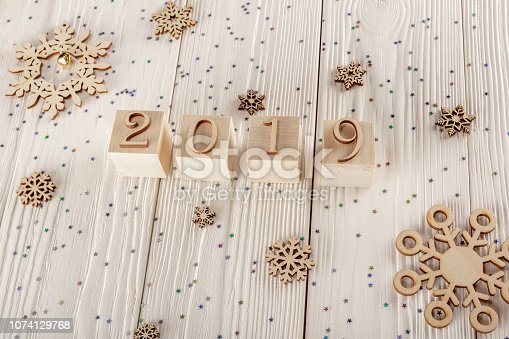 1009979852 istock photo Christmas card, wooden cubes on a wooden background. Home cozy design. Happy new year 2019. 1074129768