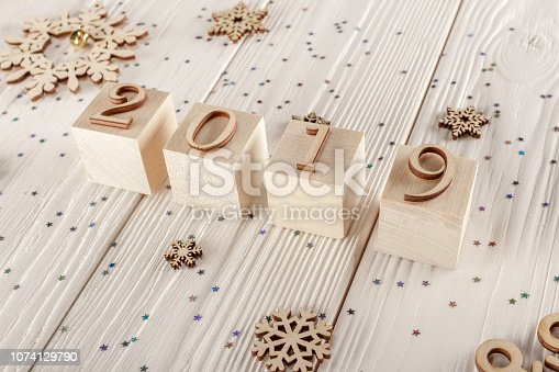 1009979852 istock photo Christmas card, wooden cubes on a wooden background. Home cozy design. Happy new year 2019. 1074129790