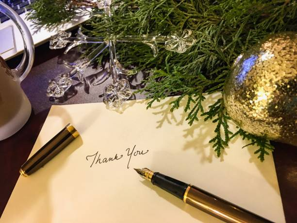 Christmas card writing thank you with evergreen  and ornaments background stock photo