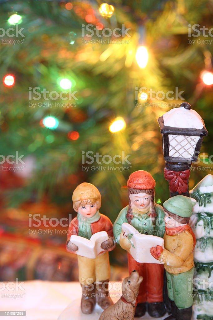 Christmas carolers figurines over a Christmas background stock photo