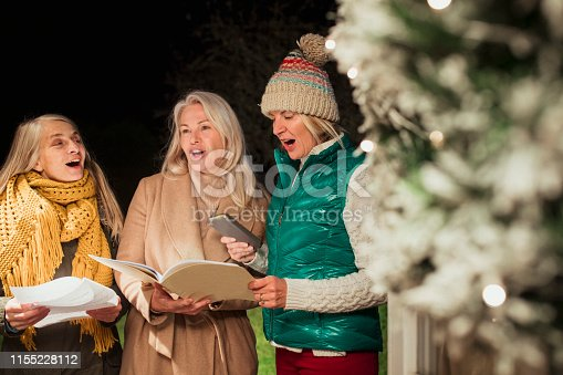 Group of three women dressed warmly standing at a front door holding books as they Christmas carol.