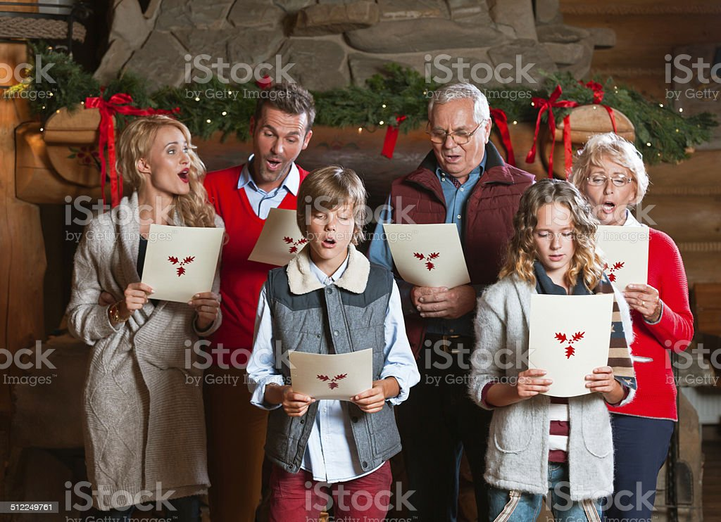 Christmas Carols Happy multi generation family: grandparents, parents and children standing in front of fireplace at home and singing carols. Active Seniors Stock Photo