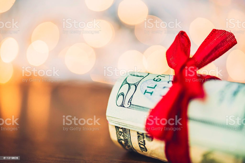 Christmas cash. Wad of American currency tied with red ribbon stock photo