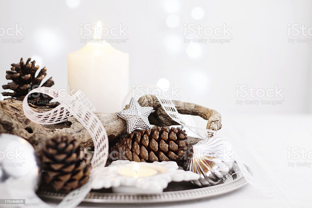 Christmas centerpiece with candles, pine cones, branch and silver decor stock photo