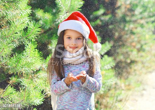 istock Christmas child in santa red hat blowing on snow 501814118