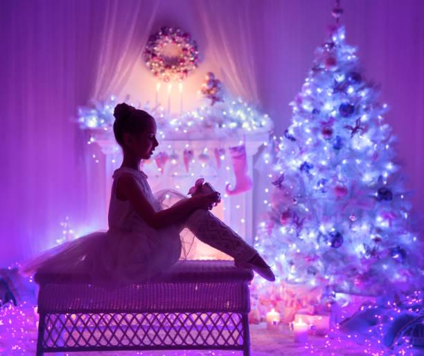 weihnachten kind offen präsent geschenk-box vor xmas tree kamin, mädchen kind in der nacht beleuchtung - lila mädchen zimmer stock-fotos und bilder