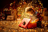 istock Christmas Child Open Present Gift, Happy Baby Boy looking to Magic Light in Box, Kid and Xmas Tree 1063239772