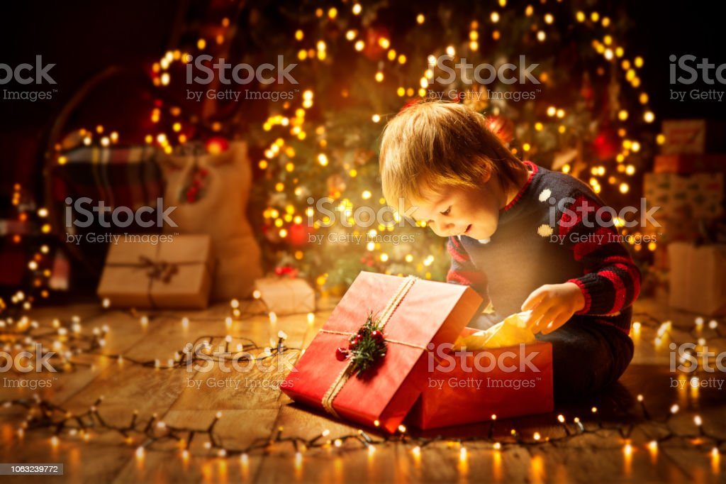 Christmas Child Open Present Gift, Happy Baby Boy looking to Magic Light in Box, Kid and Xmas Tree stock photo