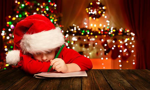weihnachten kind schreiben buchstabe santa claus, kind in weihnachtsmütze schreiben - weihnachts wunschliste stock-fotos und bilder