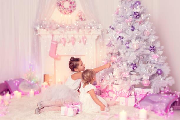 weihnachten kinder schmücken weihnachtsbaum, kind und baby mädchen im ferienhaus der familie - lila mädchen zimmer stock-fotos und bilder