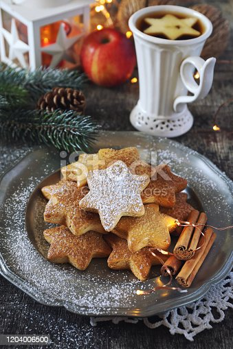 Christmas cinnamon cookies (spice-cake),  cup of tea and New Year's decoration. Rustic style
