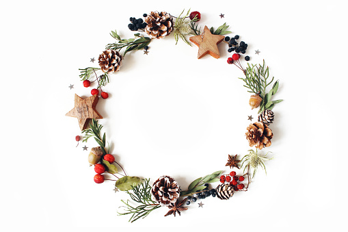 Christmas circle floral composition. Wreath of cypress, eucalyptus branches, pine cones, rowan berries, anise, confetti stars and sea holly flowers on white background, winter wedding design. Flat lay