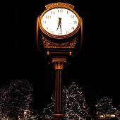 A clock in downtown Woodstock, IL against a black sky with Christmas lights