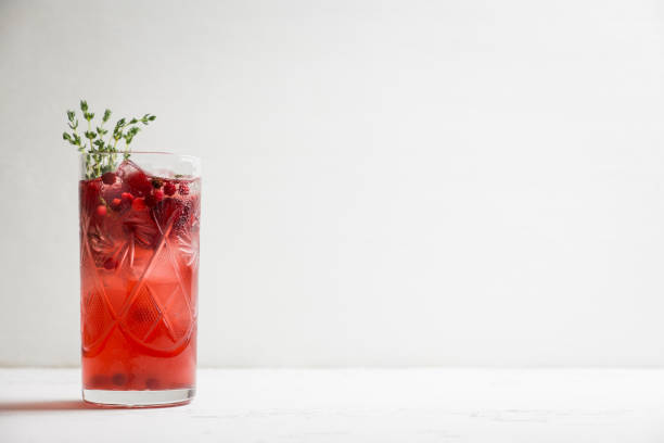 Christmas cocktail with berries and thyme on the rustic background Christmas cocktail with berries and thyme on the rustic background. Selective focus. thyme photos stock pictures, royalty-free photos & images