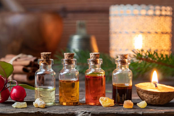 christmas collection of essential oils with frankincense, wintergreen and candles - aromaterapia zdjęcia i obrazy z banku zdjęć