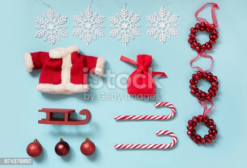 istock Christmas collection with Santa's jacket, candy canes, snowflakes, red sleid, Santa's bag for mock up template design. Christmas decorations and objects on blue. Flat lay. Top view. 874376892