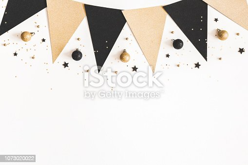 1076057502 istock photo Christmas composition. Black and golden decorations on white background. Christmas, winter, new year concept. Flat lay, top view, copy space 1073020022