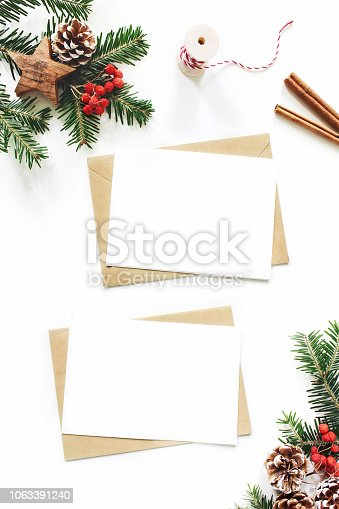 istock Christmas composition. Blank greeting card, envelope mock-up scene. Pine cones, fir tree branches, red rowan berries and wooden stars on white table background. Flat lay, top view, vertical. 1063391240