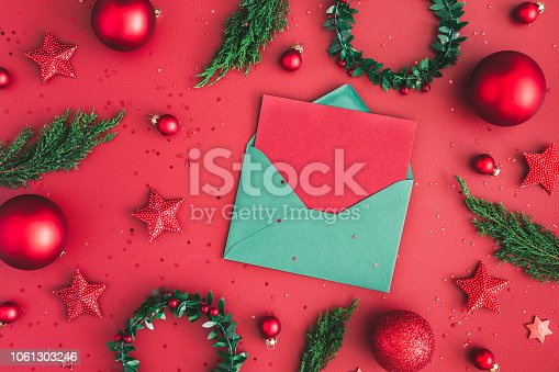 1062680370 istock photo Christmas composition. Christmas decorations, fir tree branches, envelope on red background. Flat lay, top view, copy space 1061303246